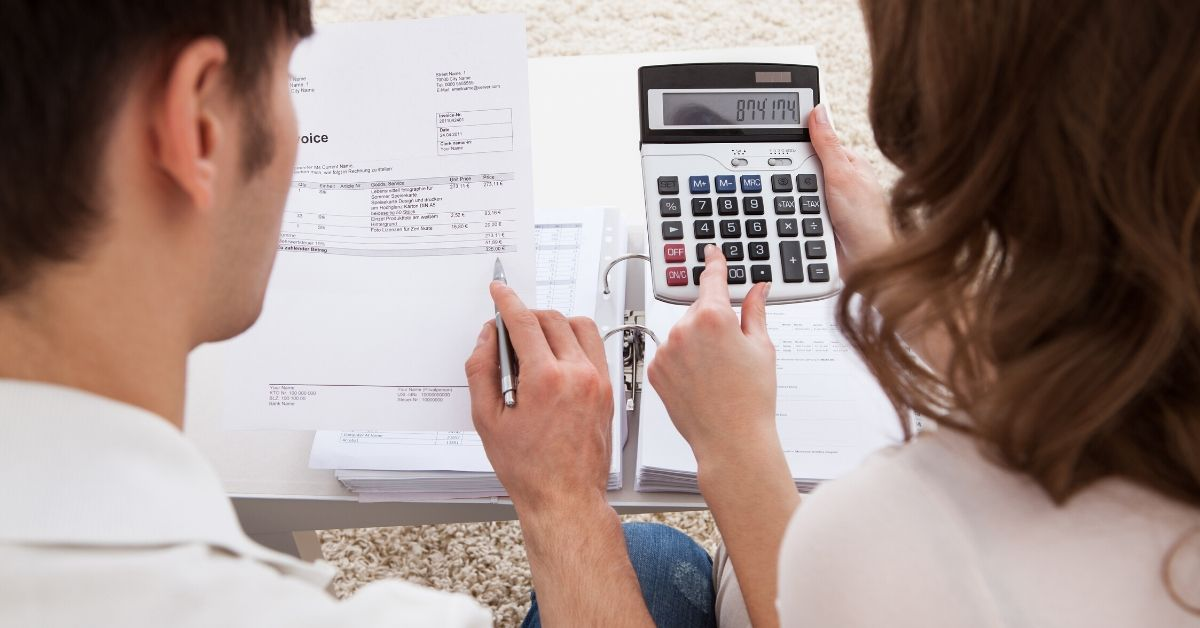 Budgeting Basics Using Last Month's Income - picture of back of couple working on budget with calculator