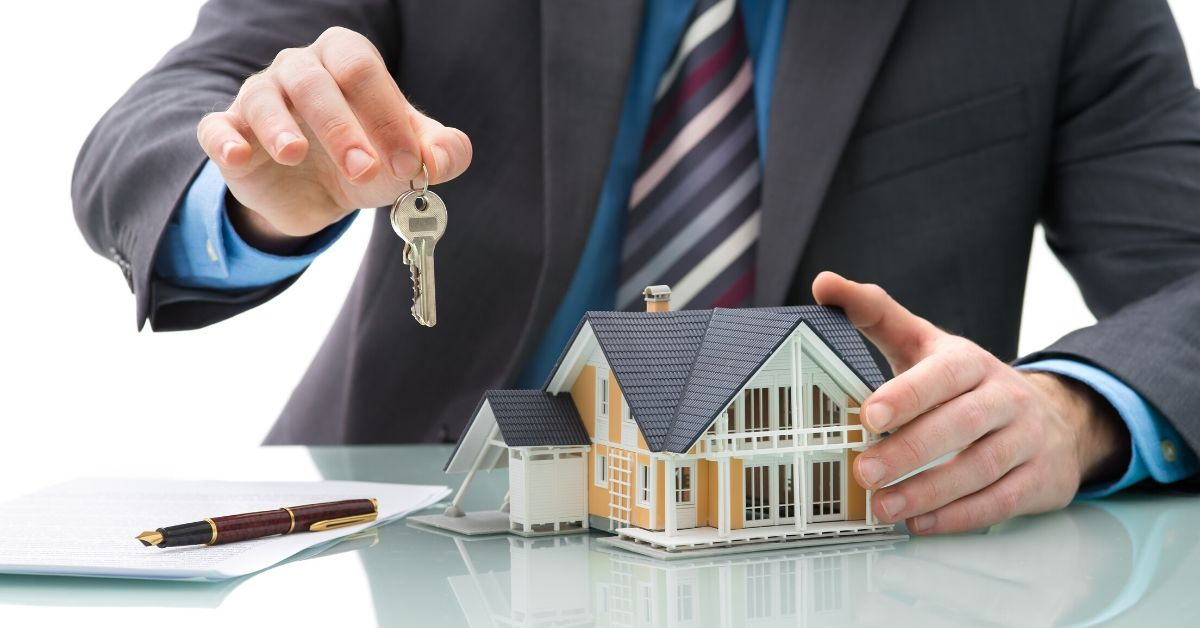Avoid 30 Year Mortgage Trap - picture of little house on table and someone holding out a key