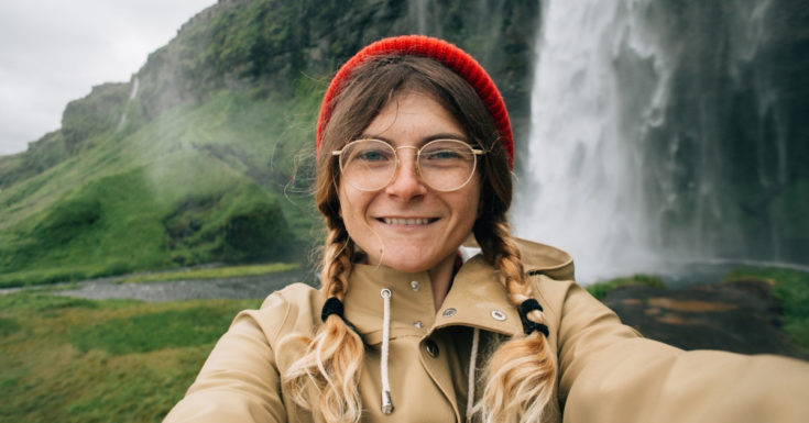Atlas Travel Insurance Review - selfie picture of woman in hat with waterfall behind her