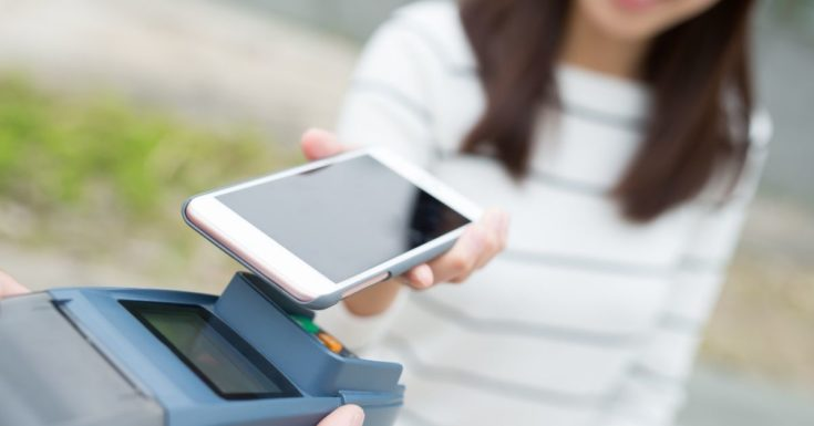 Best Checking Accounts - picture of woman paying with smartphone