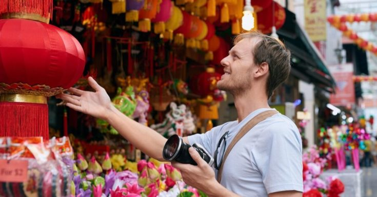 SafetyWing Review - picture of man at street fair in Asia
