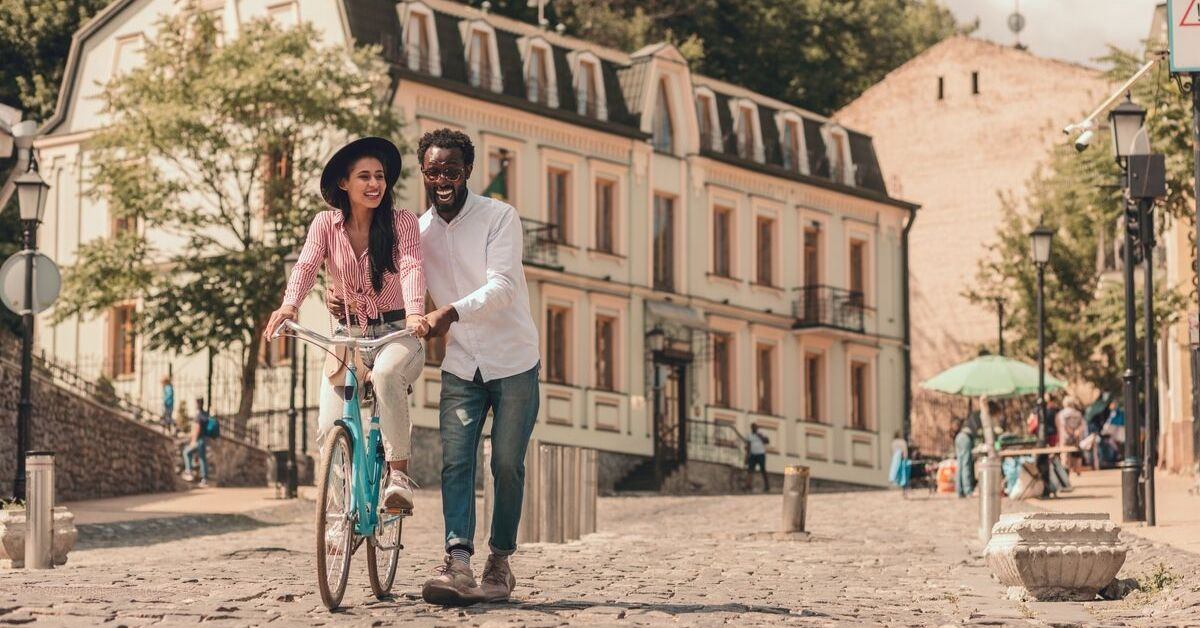 Taxes While Traveling - picture of couple biking on cobbled street